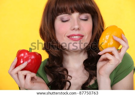 Woman  with eyes closed holding peppers