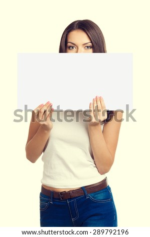 woman with face covering by signboard or paper card, with empty blank copyspace area for text or slogan. Caucasian model looking over small poster. - stock photo
