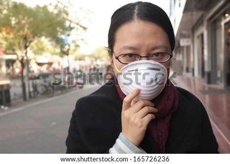 Woman with face mask on a polluted city street - stock photo