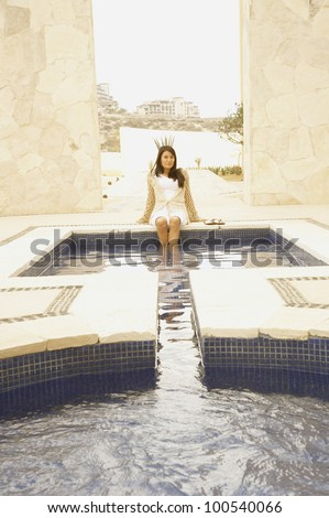Woman with feet in outdoor hot tub - stock photo