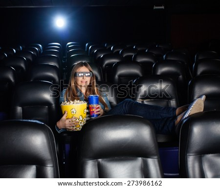 Woman with feetup on seat holding snacks while watching 3D movie at cinema theater - stock photo