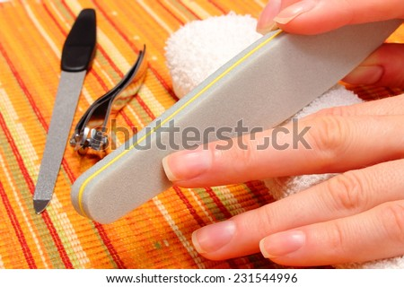 Woman with file filing nails, woman polishing nails, manicure, nail care - stock photo