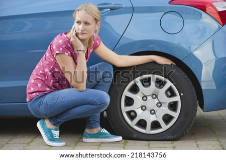 Woman With Flat tire On Car Phoning For Assistance - stock photo