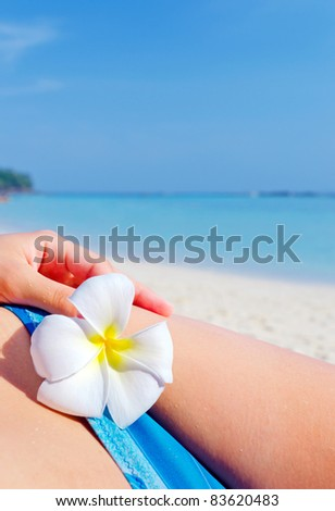 Woman with flower on the beach.