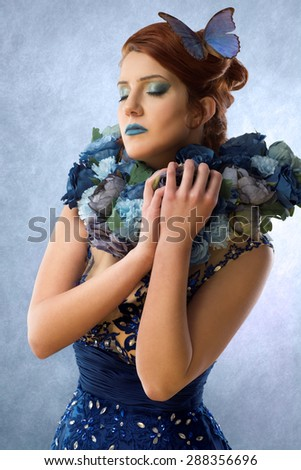 Woman with flowers and butterfly - stock photo