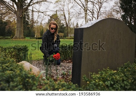 Woman with flowers crouching at cemetery - stock photo