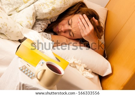Woman with flu resting in bed - stock photo