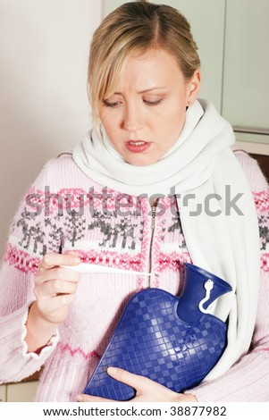 Woman with flu taking her temperature, looking at the thermometer having a hot water bag in her hand - stock photo