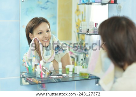 Woman with fresh skin of face in bathroom - stock photo