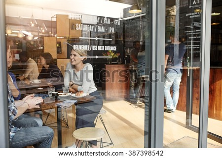 Woman with friends at a cafe seen through window - stock photo