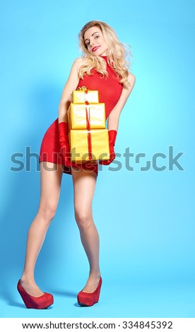 Woman with gifts boxes beauty happy. Young curly playful blonde girl smiling in fashion red dress and gloves with gold presents on blue, people. Christmas vivid holiday, celebration copyspace - stock photo