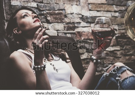 woman with glass of red wine and cigarette, wearing blue jeans and white t-shirt,   on leather couch, indoor shot - stock photo