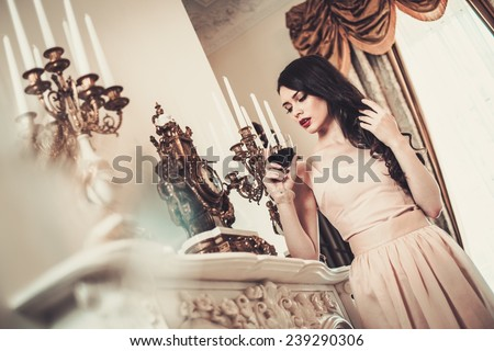 Woman with glass of red wine near fireplace in luxury house interior
