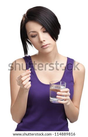 Woman with glass of water takes pills, isolated on white. Taking medication