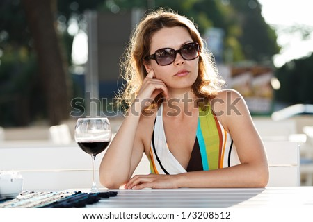 Woman with glass of wine by the sea