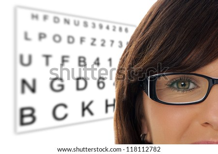 Woman with glasses at the eye doctor / Eye Test - stock photo