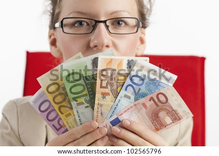 Woman with glasses is looking over a fan of notes - stock photo
