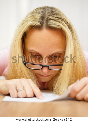 woman with glasses reading document very focused and pointing to text - stock photo