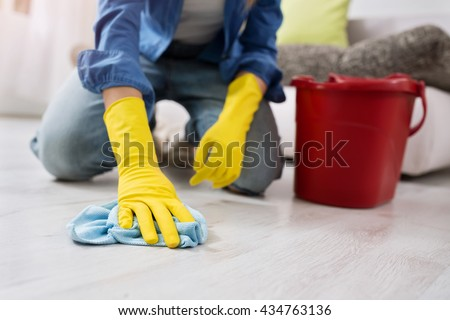 woman with gloves cleans the floor close up - stock photo