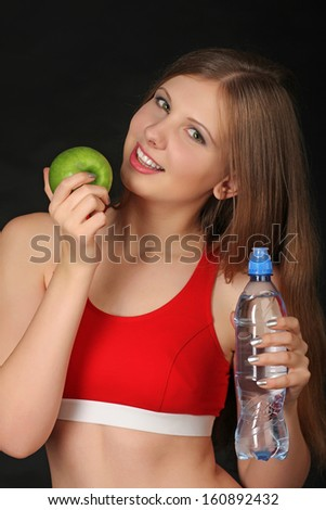 Woman with green apple and bottle of mineral water - stock photo