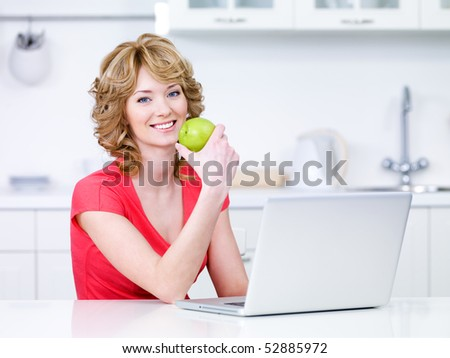 Woman with green apple and laptop sitting in the kitchen - indoors - stock photo