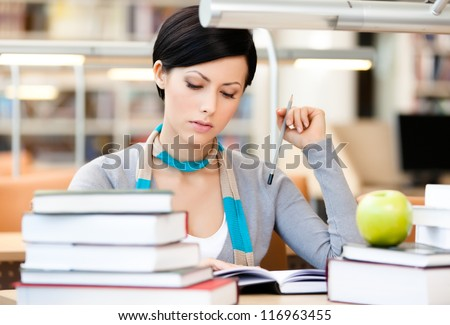 Woman with green apple surrounded with piles of books reads sitting at the table at the library. Educational process