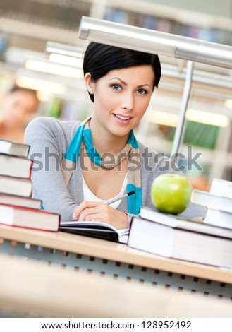 Woman with green apple surrounded with piles of books reads sitting at the table at the library. Learning process