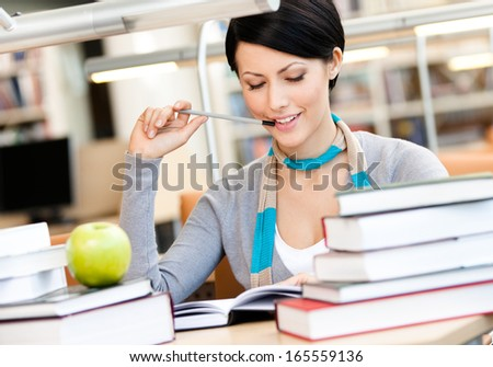 Woman with green apple surrounded with piles of books reads sitting at the table at the library. Training process