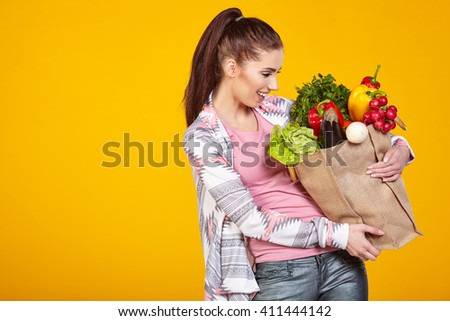 woman with green vegan food. Shopping bag. surprise emotion. Yellow background.