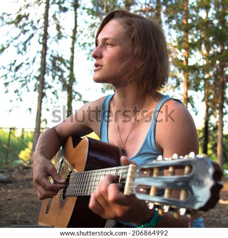 Woman with guitar closeup on a background of forest - stock photo