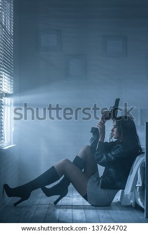 Woman with gun in hand is sitting by the bed in the darkness - stock photo