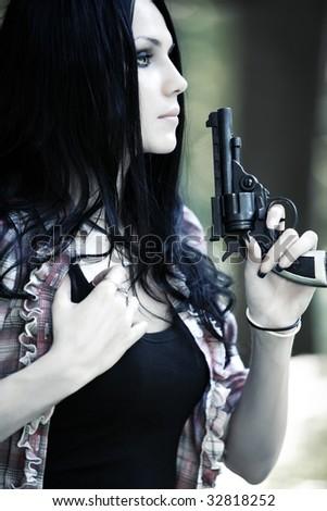 Woman with gun portrait. Shallow dof. - stock photo