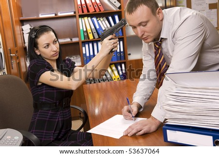 Woman with gun urging businessman to sign document - stock photo