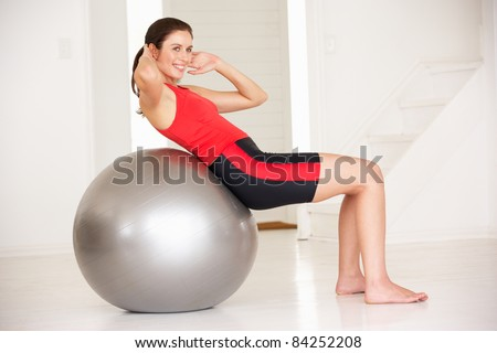 Woman with gym ball in home gym