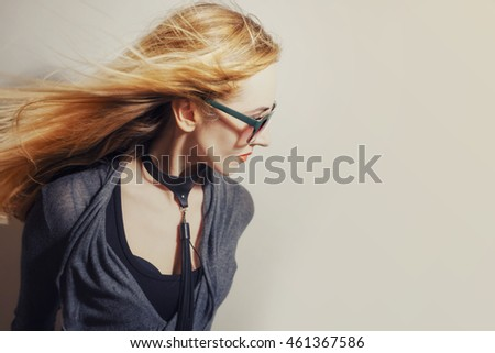 Woman with hair blowing in wind on white studio background