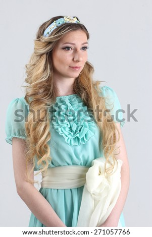 Woman with hair in curly braided hairstyle, wearing a romantic blue turquoise dress - stock photo