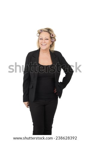 Woman with hair rollers wearing a black suit getting ready against a white background - stock photo