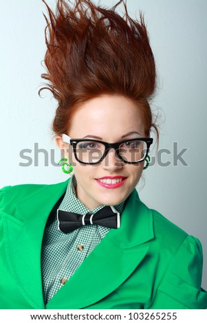 woman with hair stand on end in glasses, green coat and bow tie