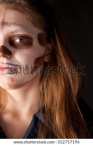 Woman with halloween make up looking to the camera - stock photo
