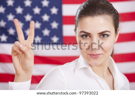 woman with hand victory sign over american flag - stock photo