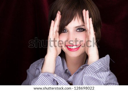 Woman with hands against cheeks with black background - stock photo