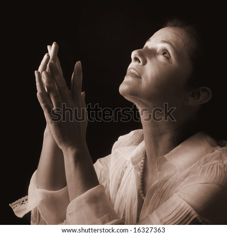 Woman with hands folded in prayer, looking up to a heavenly light - stock photo