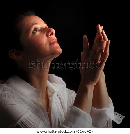 Woman with hands folded in prayer, looking up toward the Light - stock photo