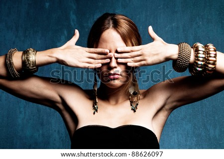 woman with hands on the eyes and lot of bracelets, studio shot - stock photo