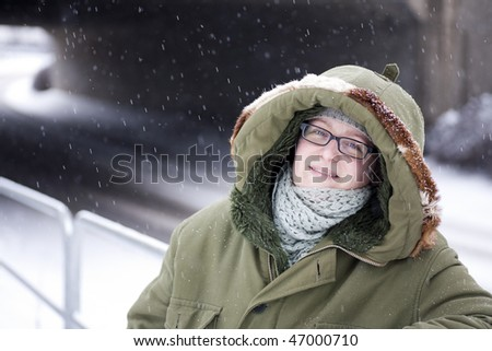 Woman with happy expression posing in warm clothes in snow - stock photo