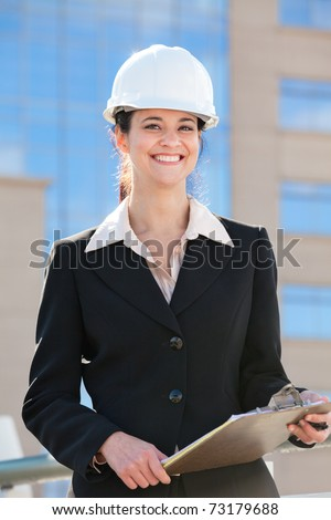 Woman with hard hat and clipboard - stock photo