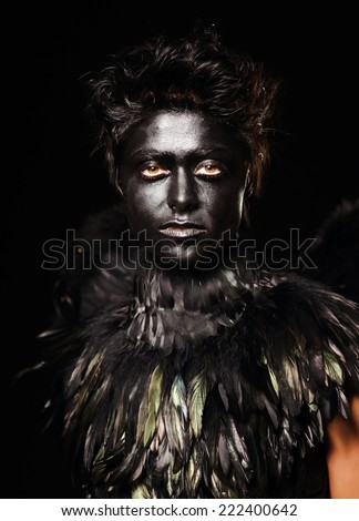Woman with harpy makeup - mystical creature, isolated on black - stock photo