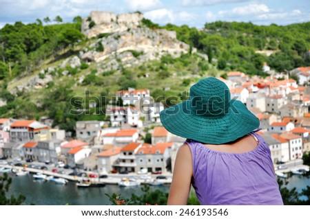 Woman with hat admiring cityscape. Novigrad, Croatia - stock photo