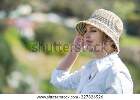 Woman with hat enjoying in nature and looking far - stock photo