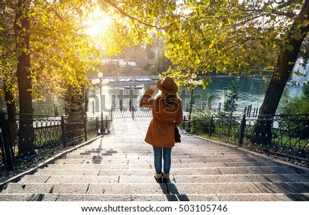 Woman with hat near the lake with yellow autumn trees in the park